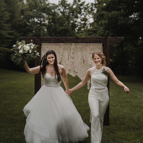 Lesbian brides Liz + Steph leap with joy in front of their outdoor alter in the Niagara region