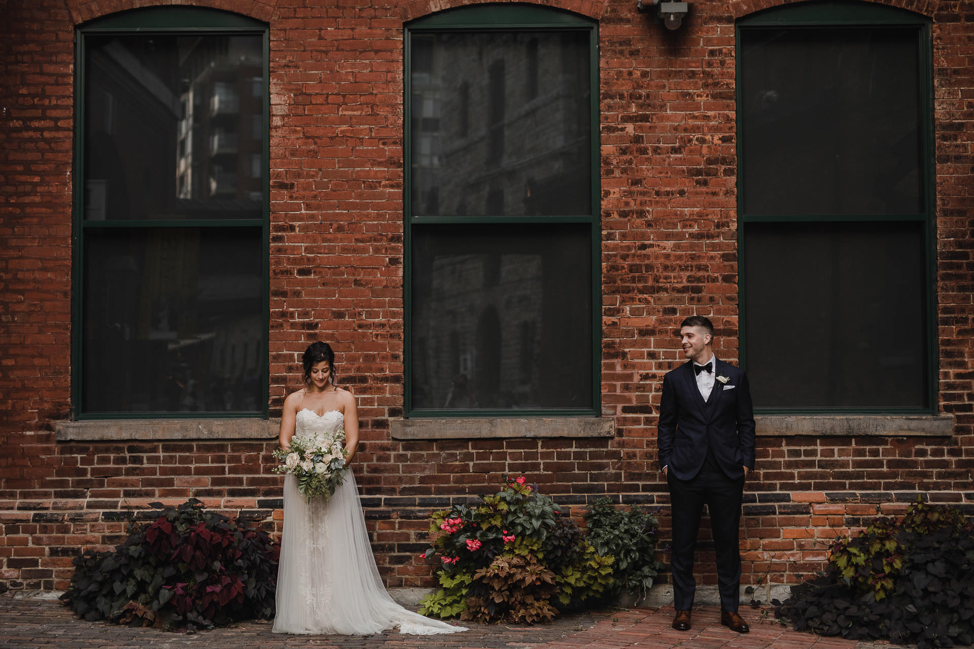 Distillery District Wedding - bride and groom in front of brick wall with windows