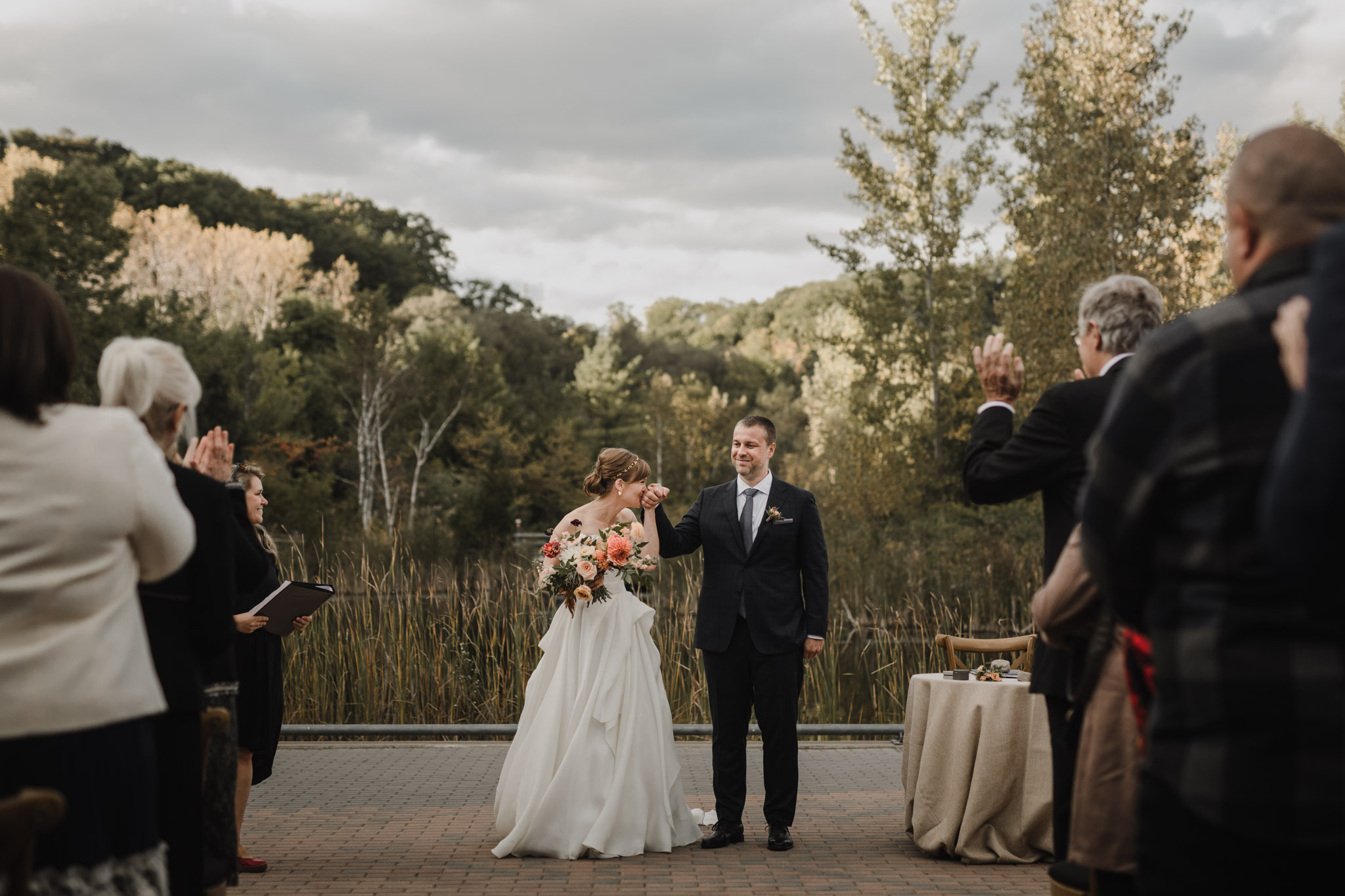 Evergreen Brickworks wedding photographer - bride kisses grooms hand