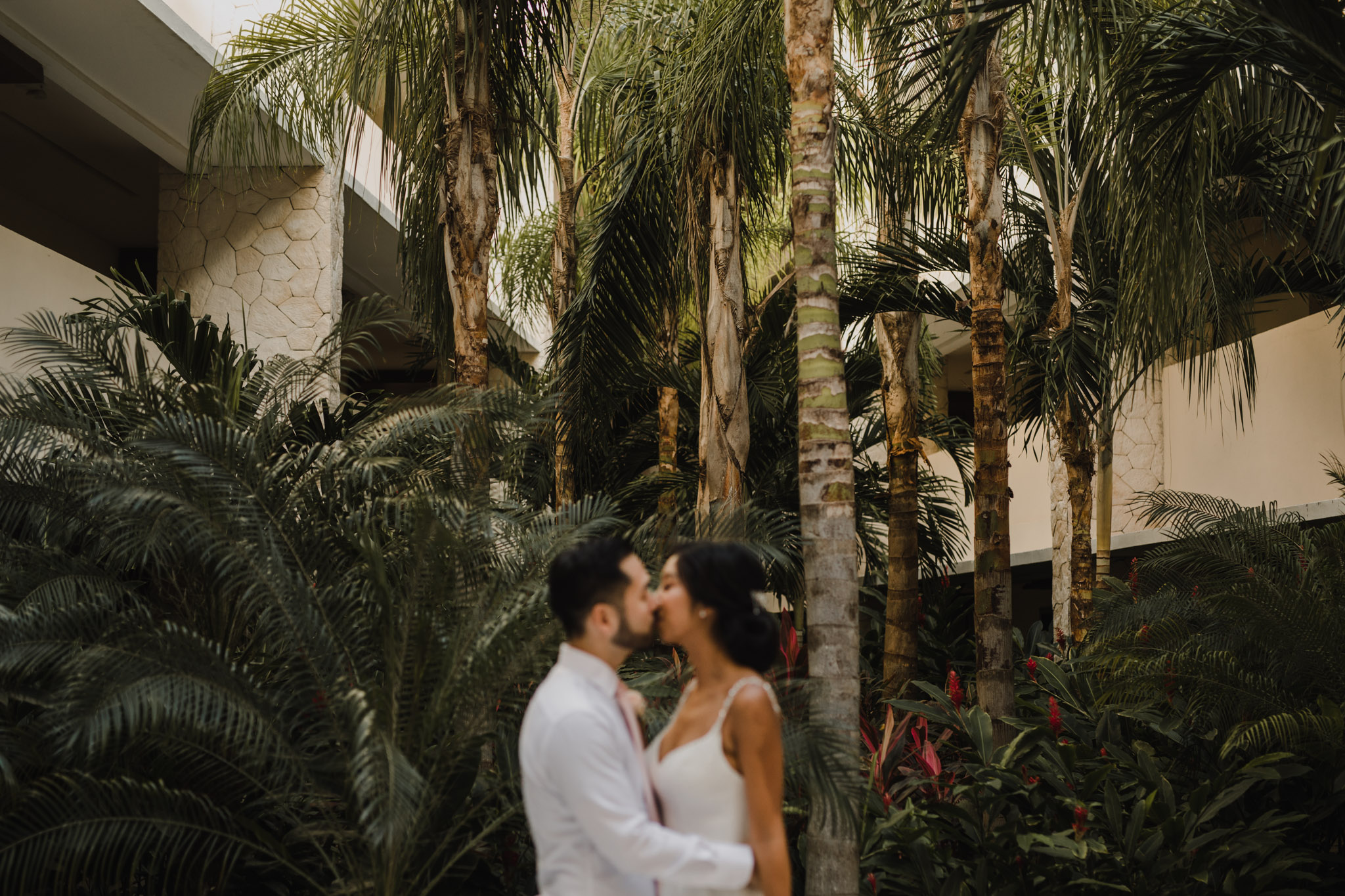 Cancun Mexico Wedding - bride and groom kiss under palm trees
