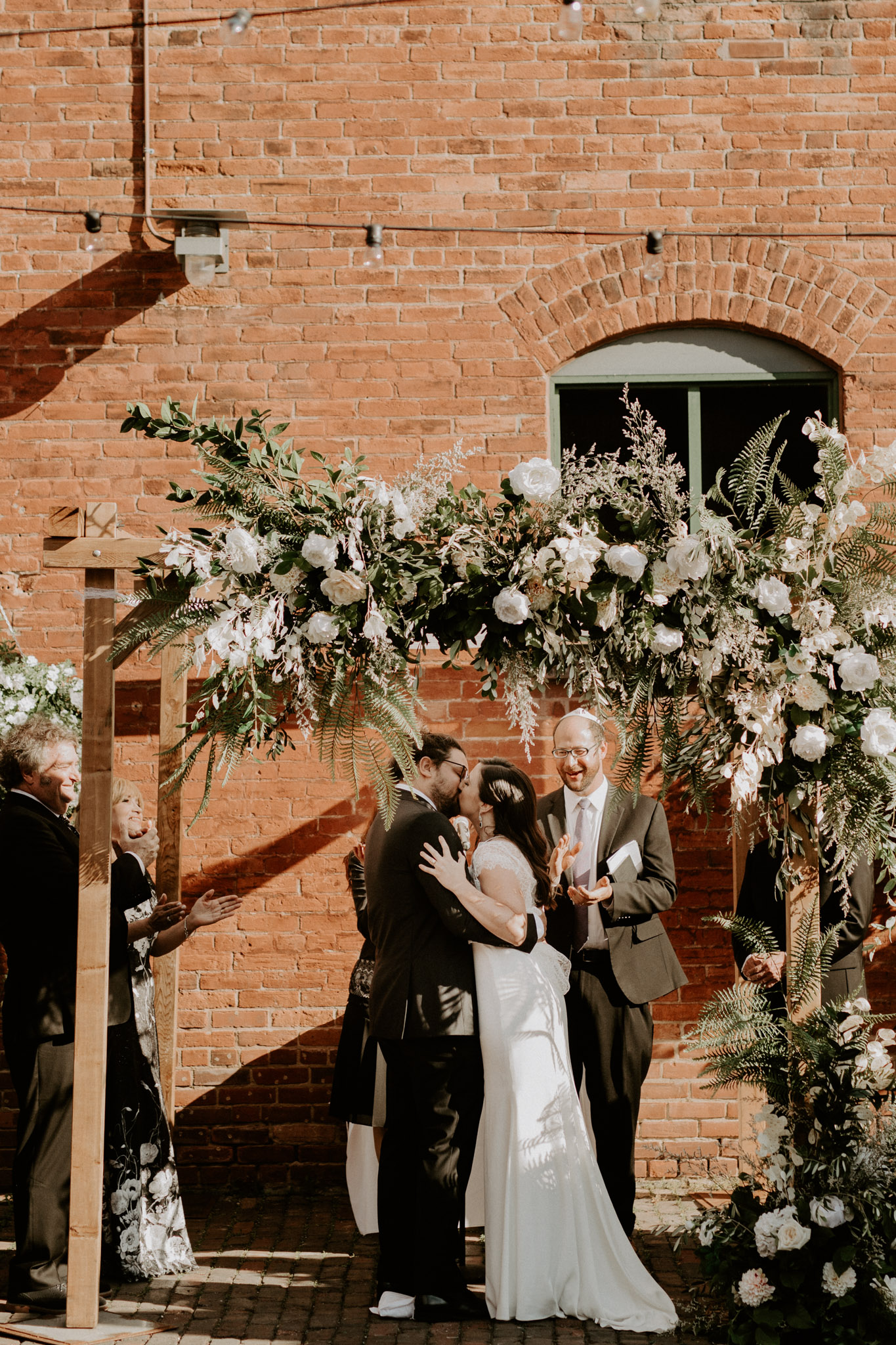 Archeo Wedding Distillery District - Newlyweds First Kiss - White Rose Alter Florist Tanya List