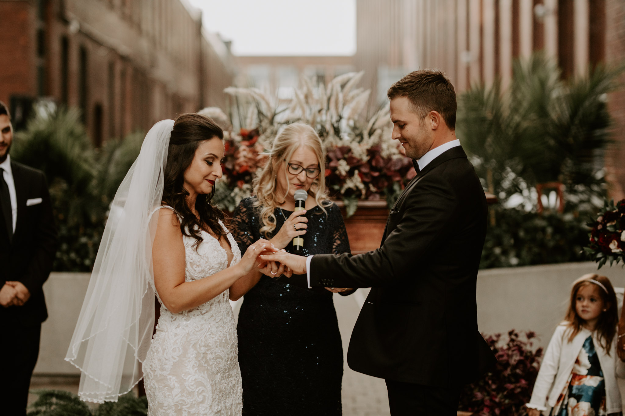 Liberty Village Wedding - bride and groom exchanging rings during outdoor ceremony