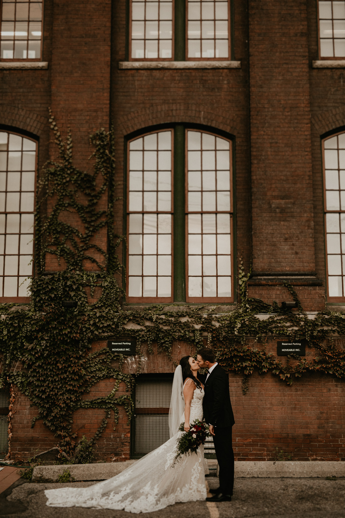 Liberty Village Wedding - newlyweds kiss in front of brick building with vines