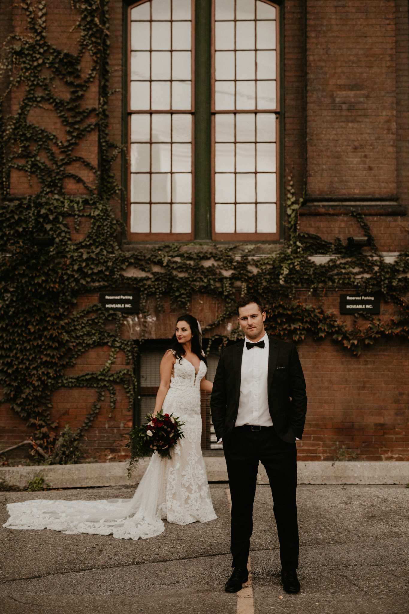 Liberty Village Wedding - Newlyweds posing in front of brick wall with ivy