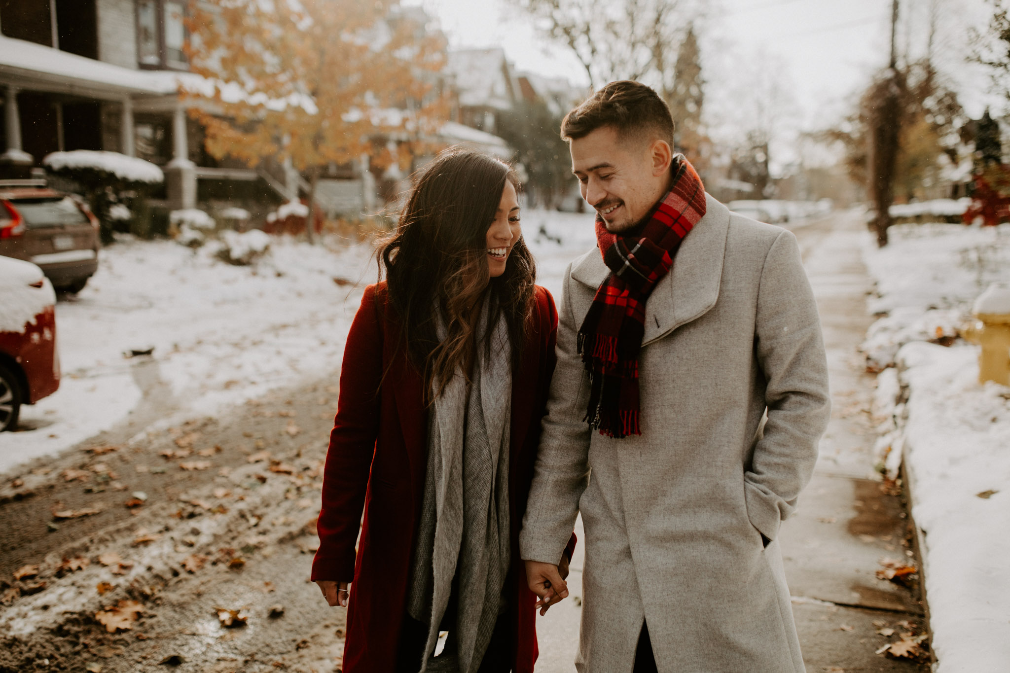 Winter Engagement in Toronto - couple walk hand in hand down snowy street