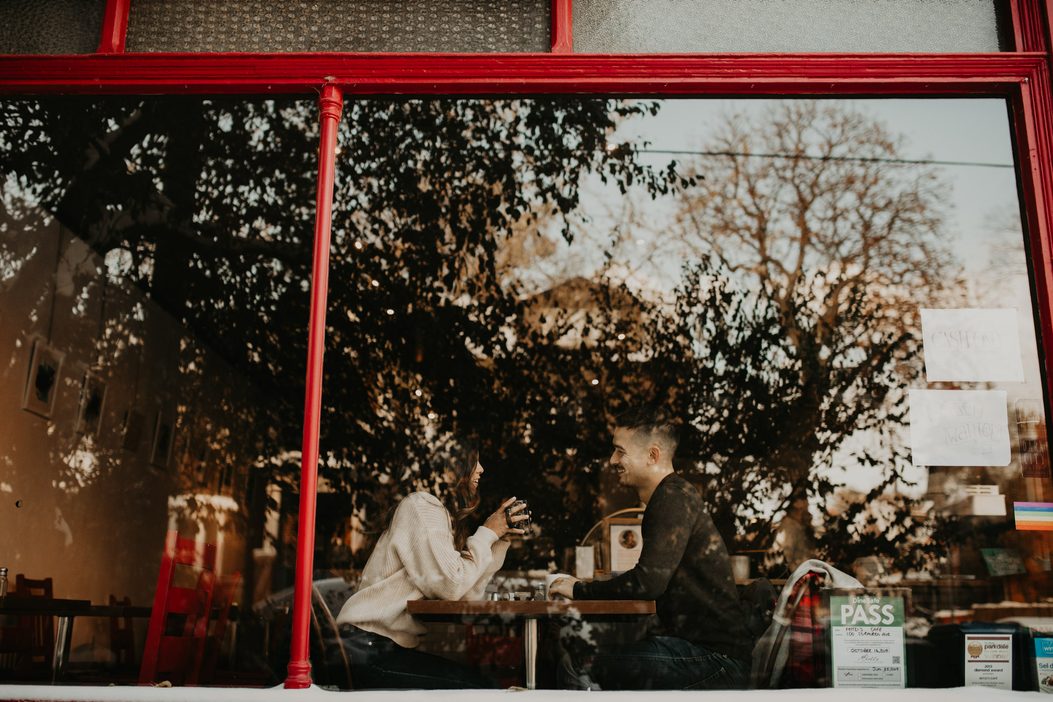 Winter Engagement in Toronto - cozy couple seen through cafe window drinking coffee