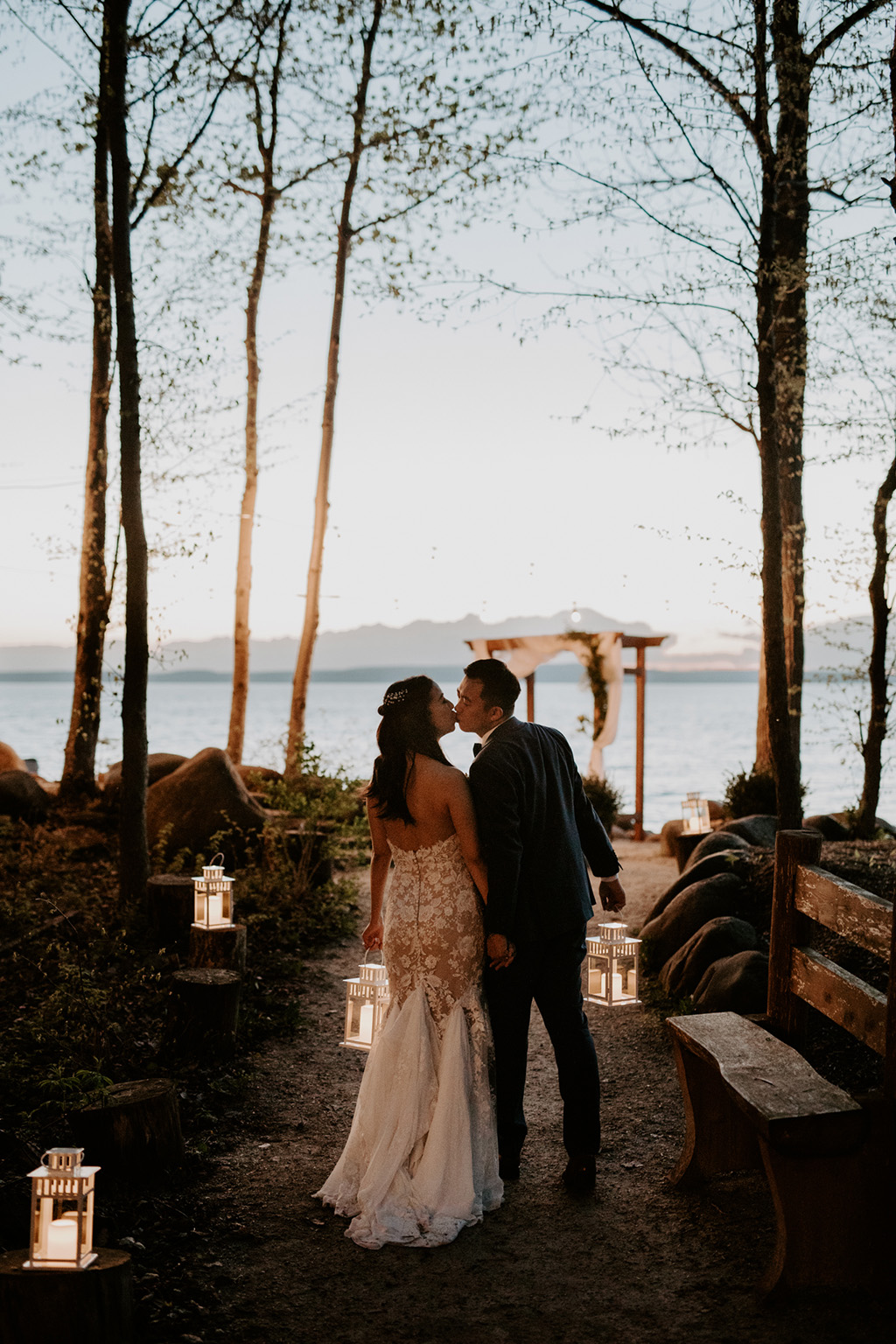 Lakeside Serenity Cottage Wedding - bride and groom kiss on tree-lined path to lake