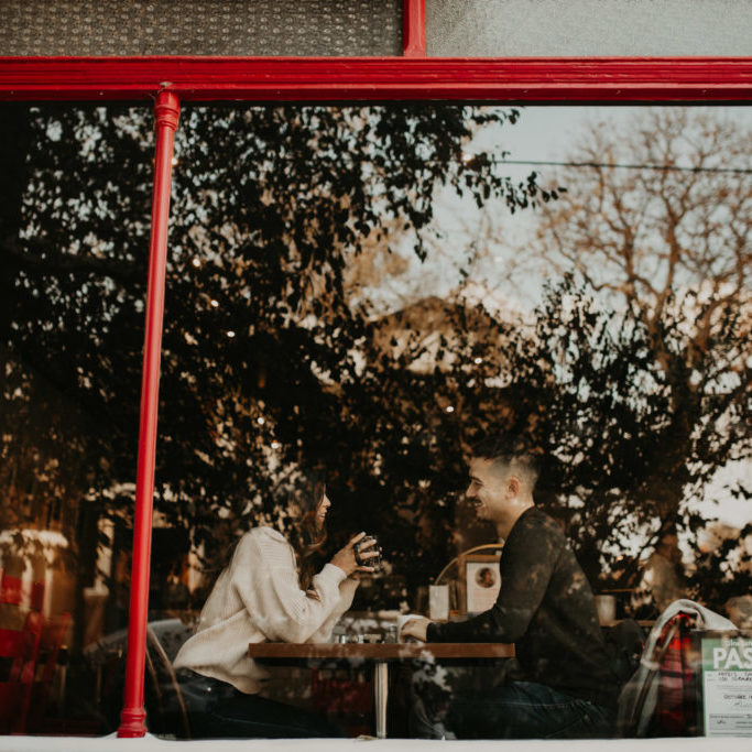 Winter Engagement in Toronto - reflections on cafe window as couple sip coffee inside