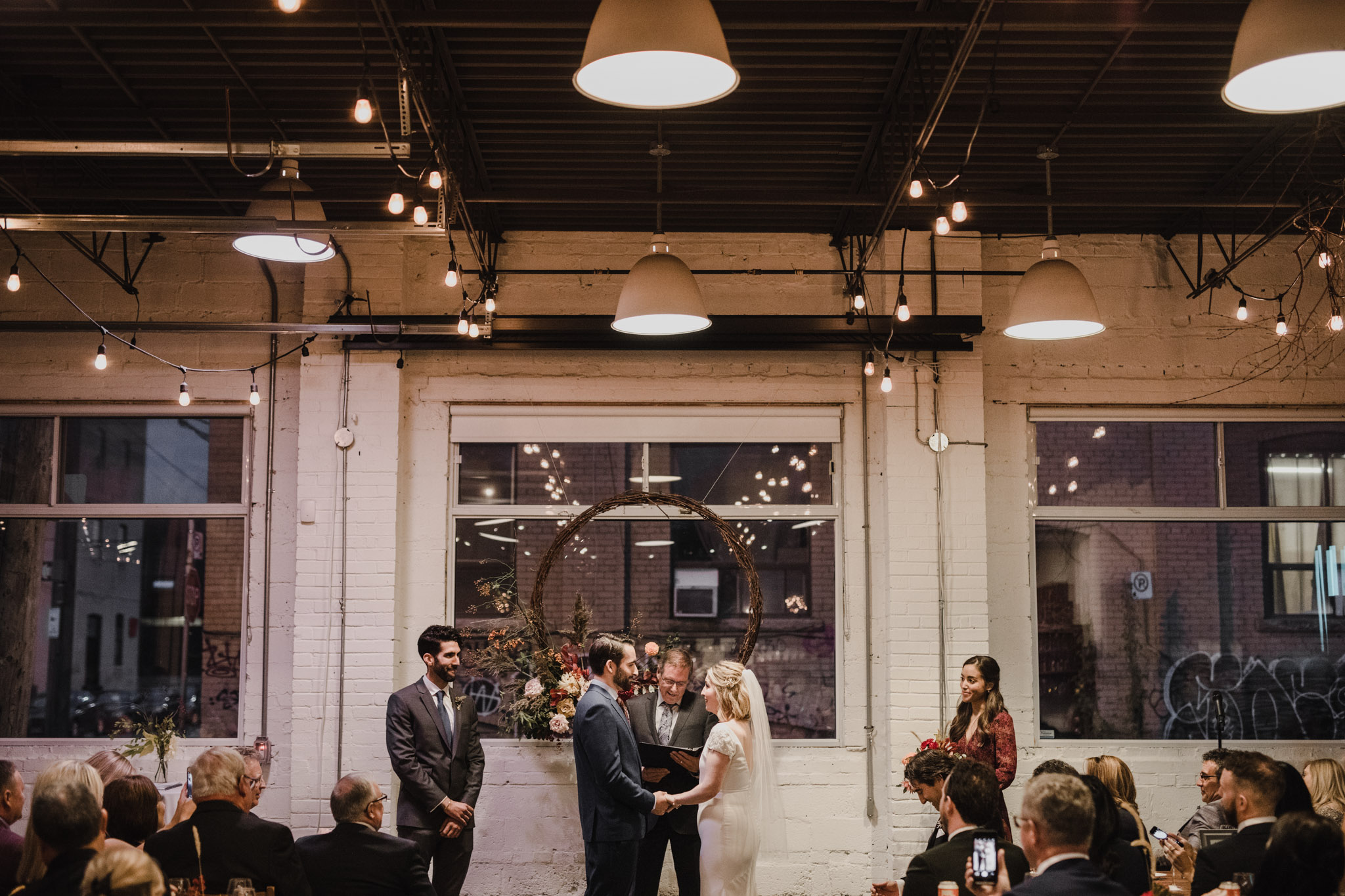 Toronto Coffee Shop Wedding - holding hands at the alter
