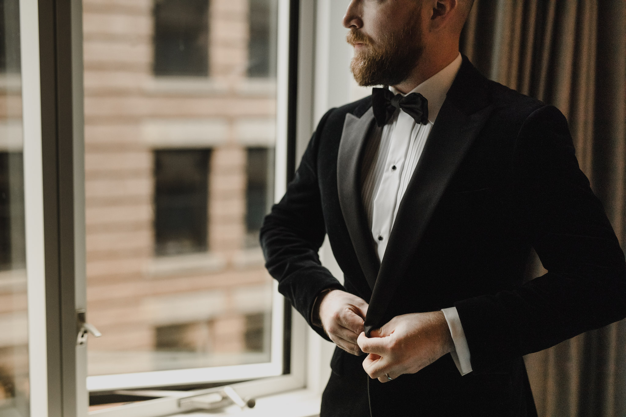 Downtown NYC Wedding - The Beekman Hotel - groom buttoning coat