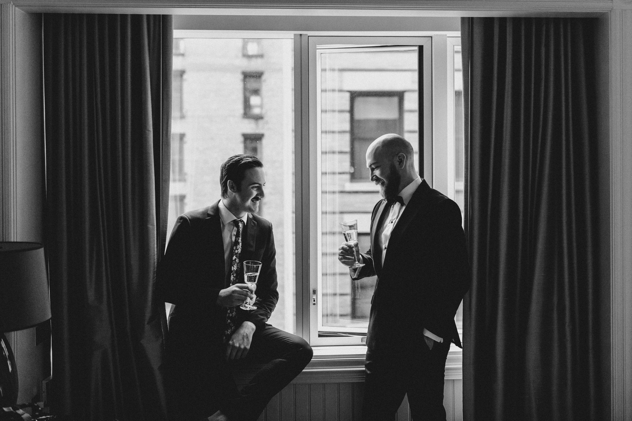 Downtown NYC Wedding - The Beekman Hotel - groom and best man in window