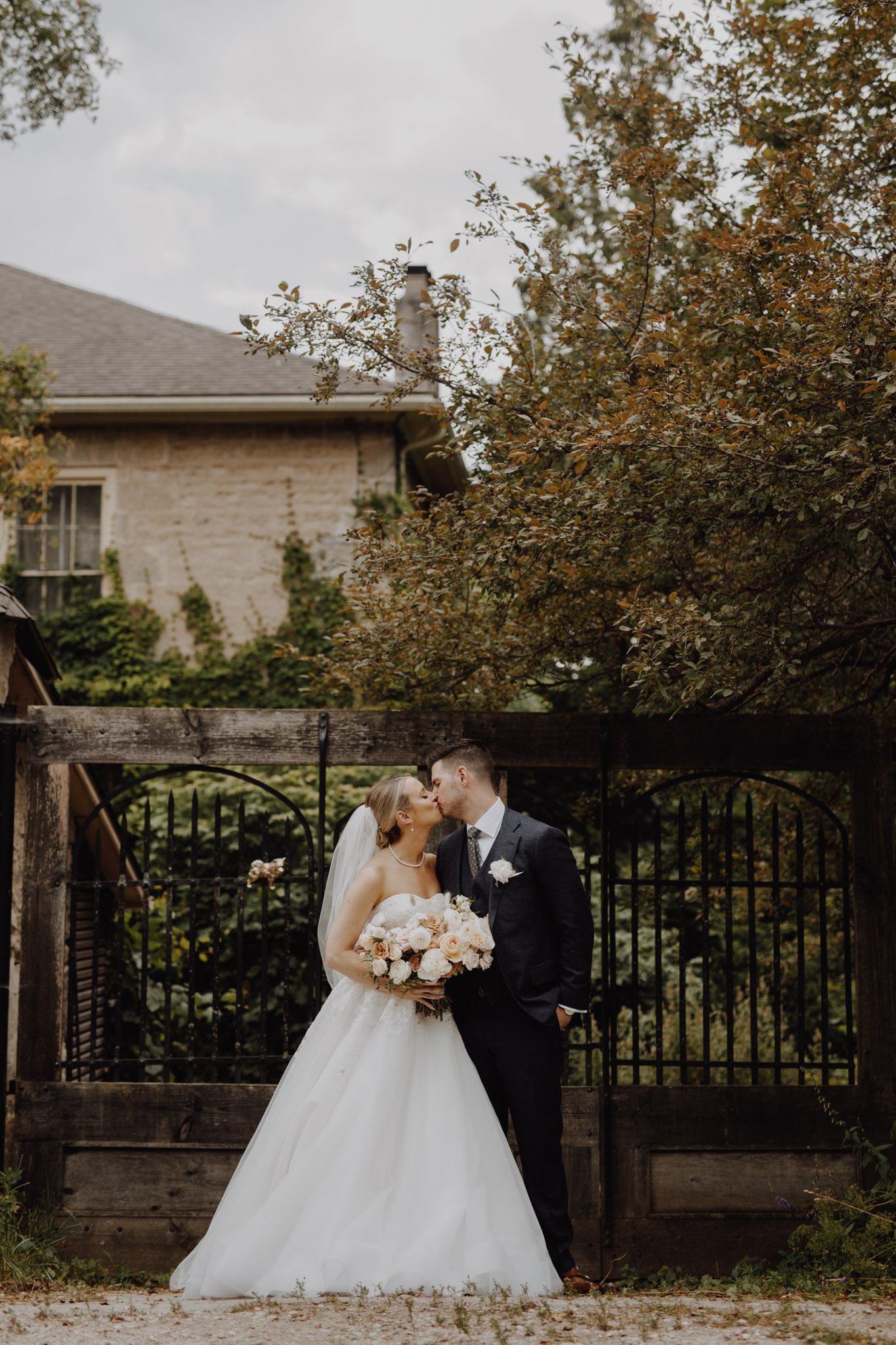 Elora Mill Wedding - bride and groom kiss by the gate