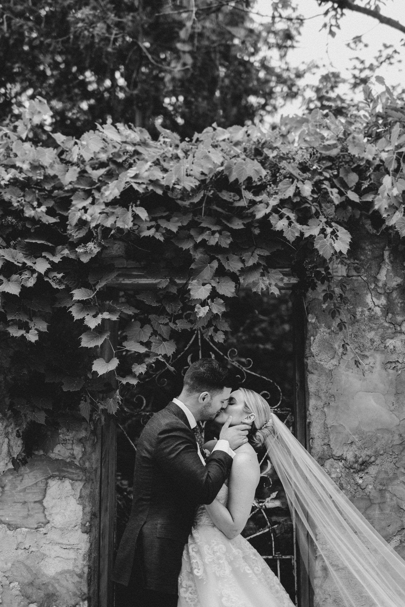 Elora Mill Wedding - bride and groom kiss in front of trellis