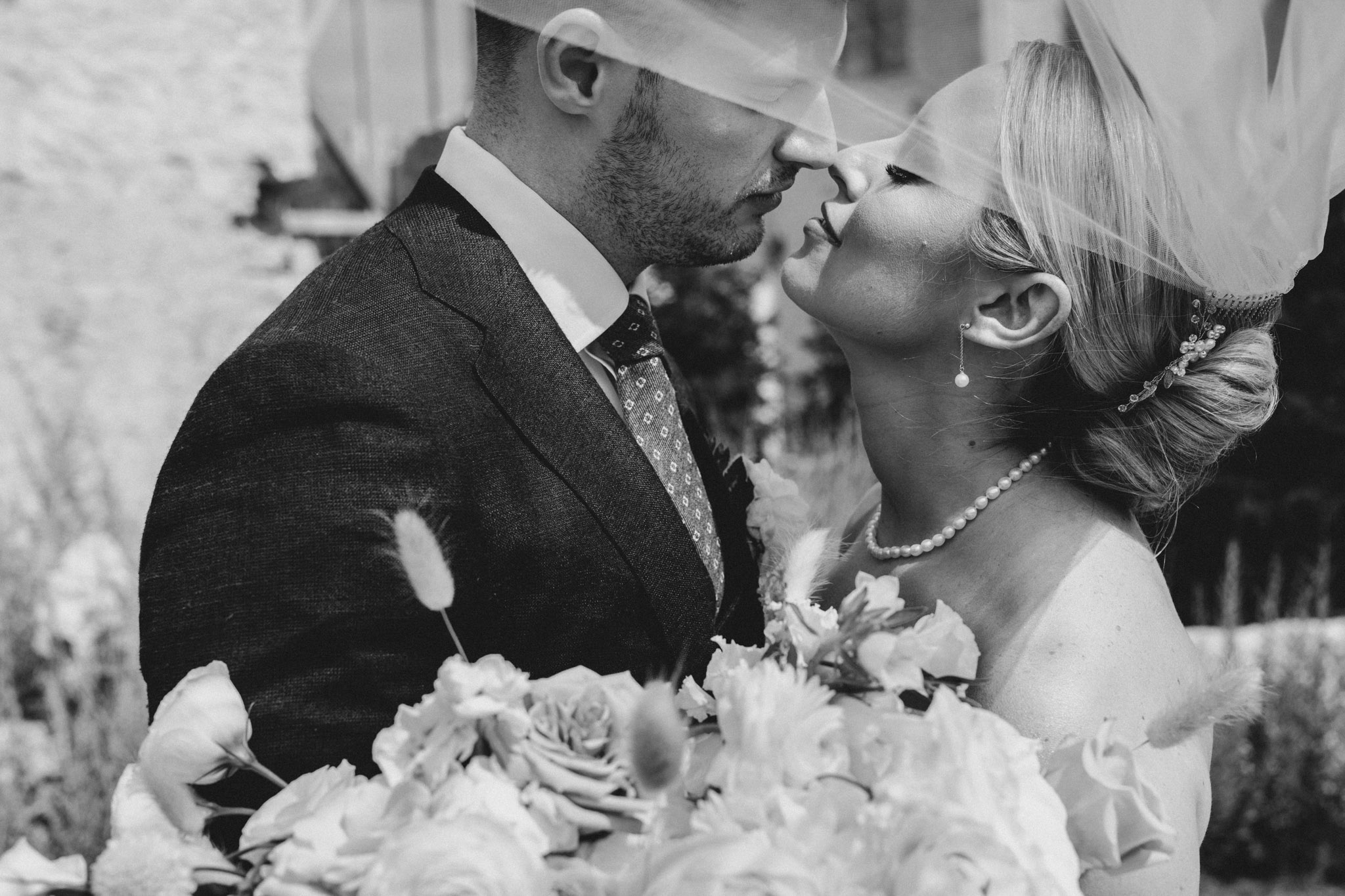Elora Mill Wedding - bride and groom kissing veil portrait