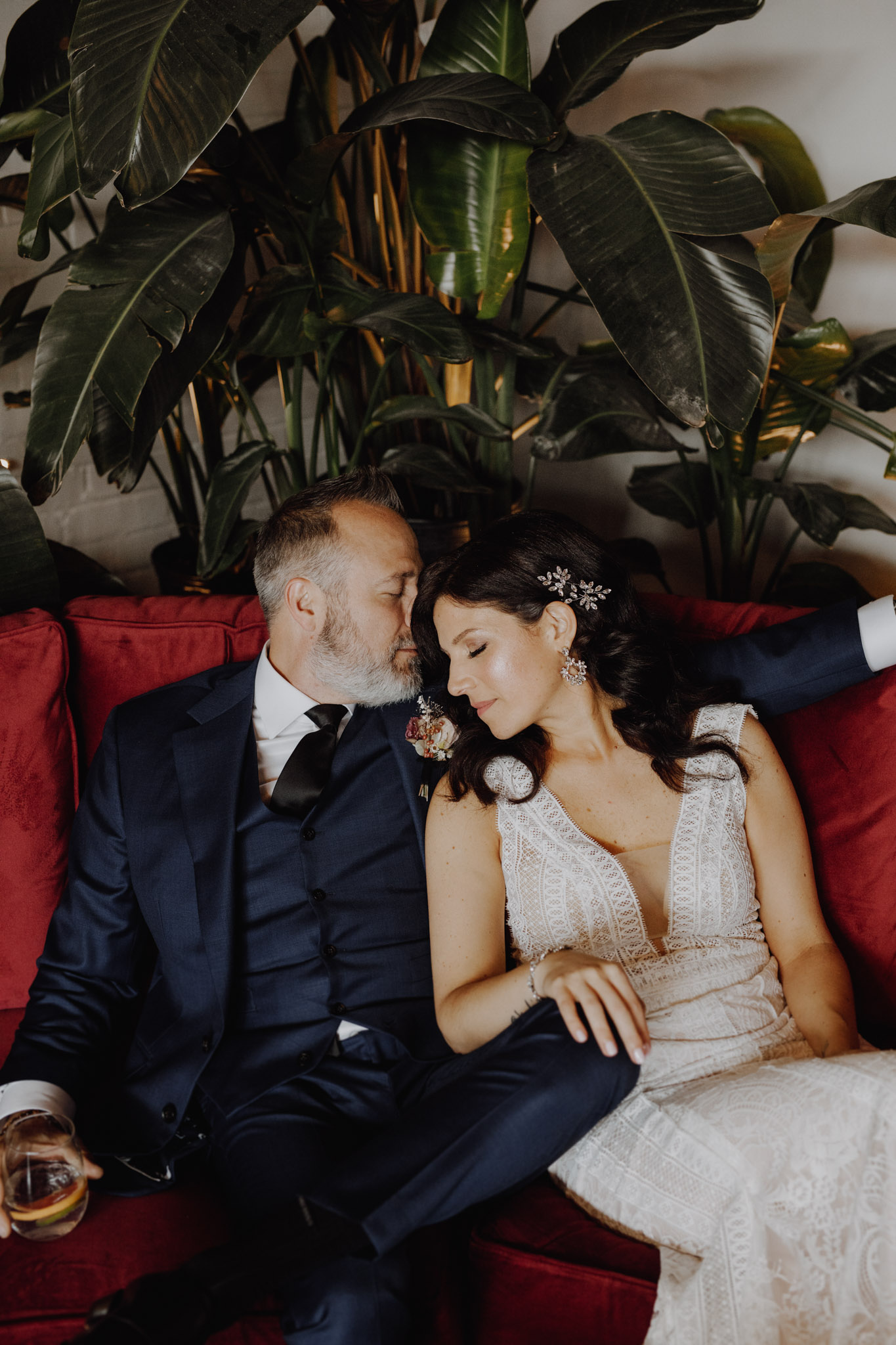 District 28 Wedding Toronto - Bride & Groom blue suit red couch