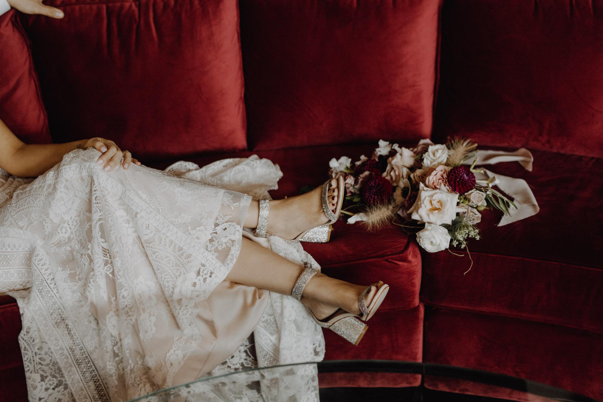 District 28 Wedding Toronto - Bride's details on red velvet couch