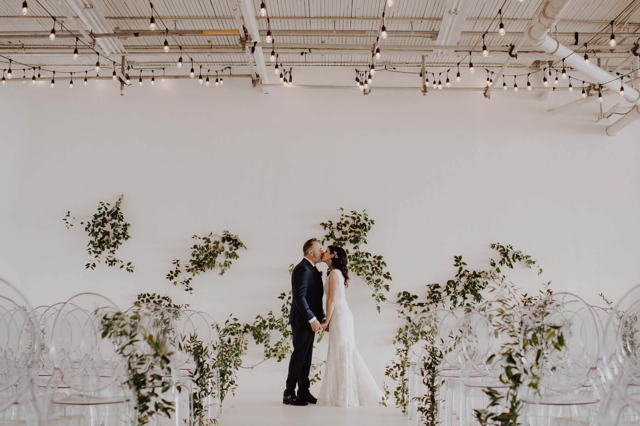 District 28 Wedding Toronto - Bride & groom kiss white backdrop
