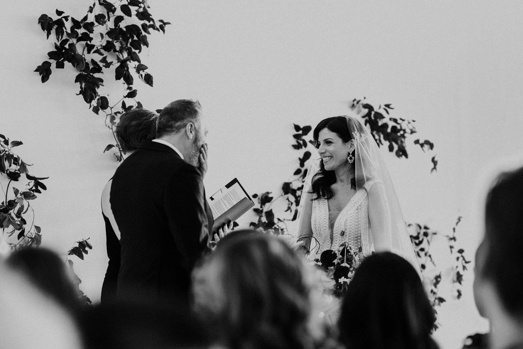 District 28 Wedding Toronto - black and white exchanging vows