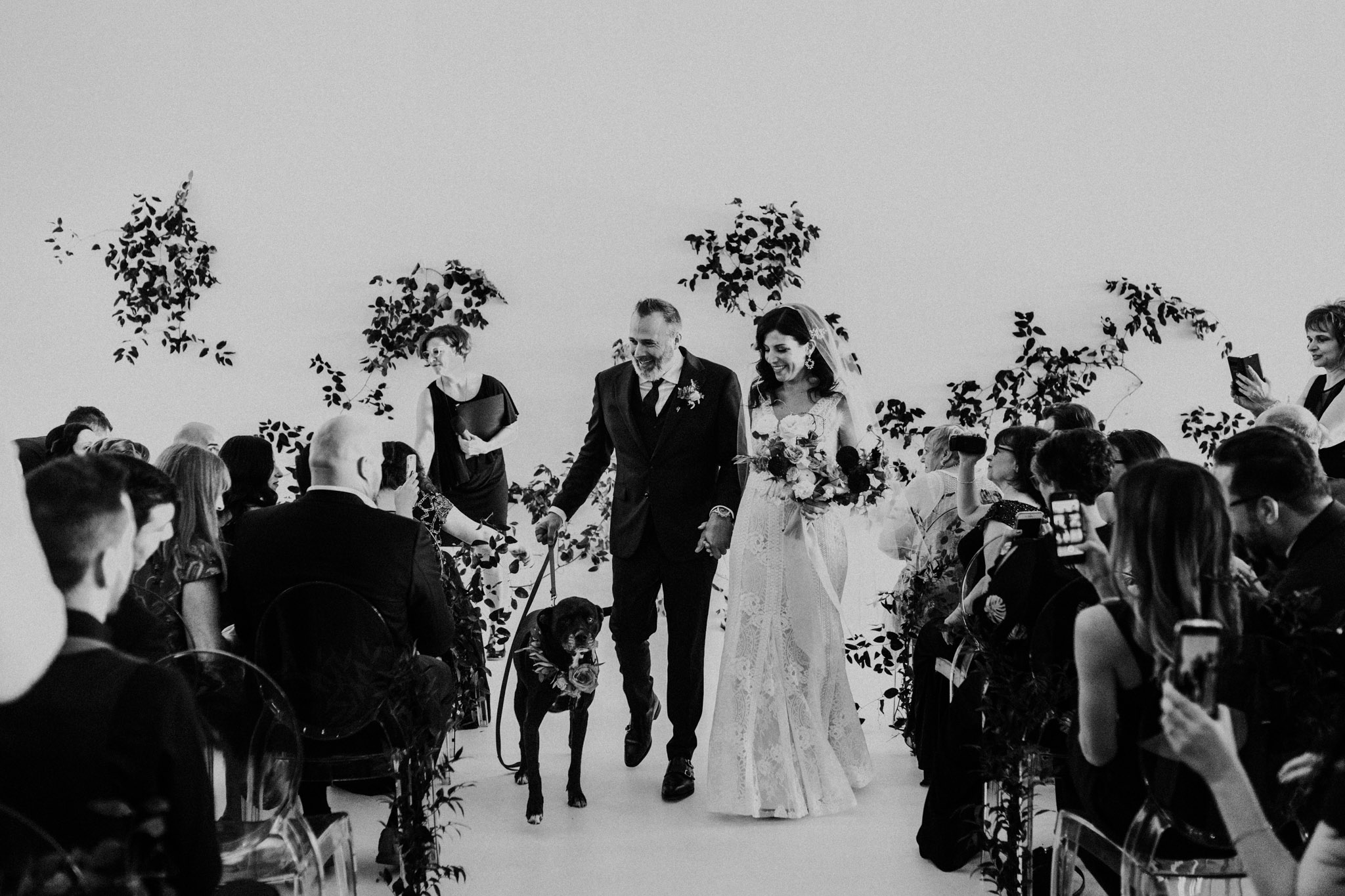 District 28 Wedding Toronto - Bride & groom walk with dog down aisle