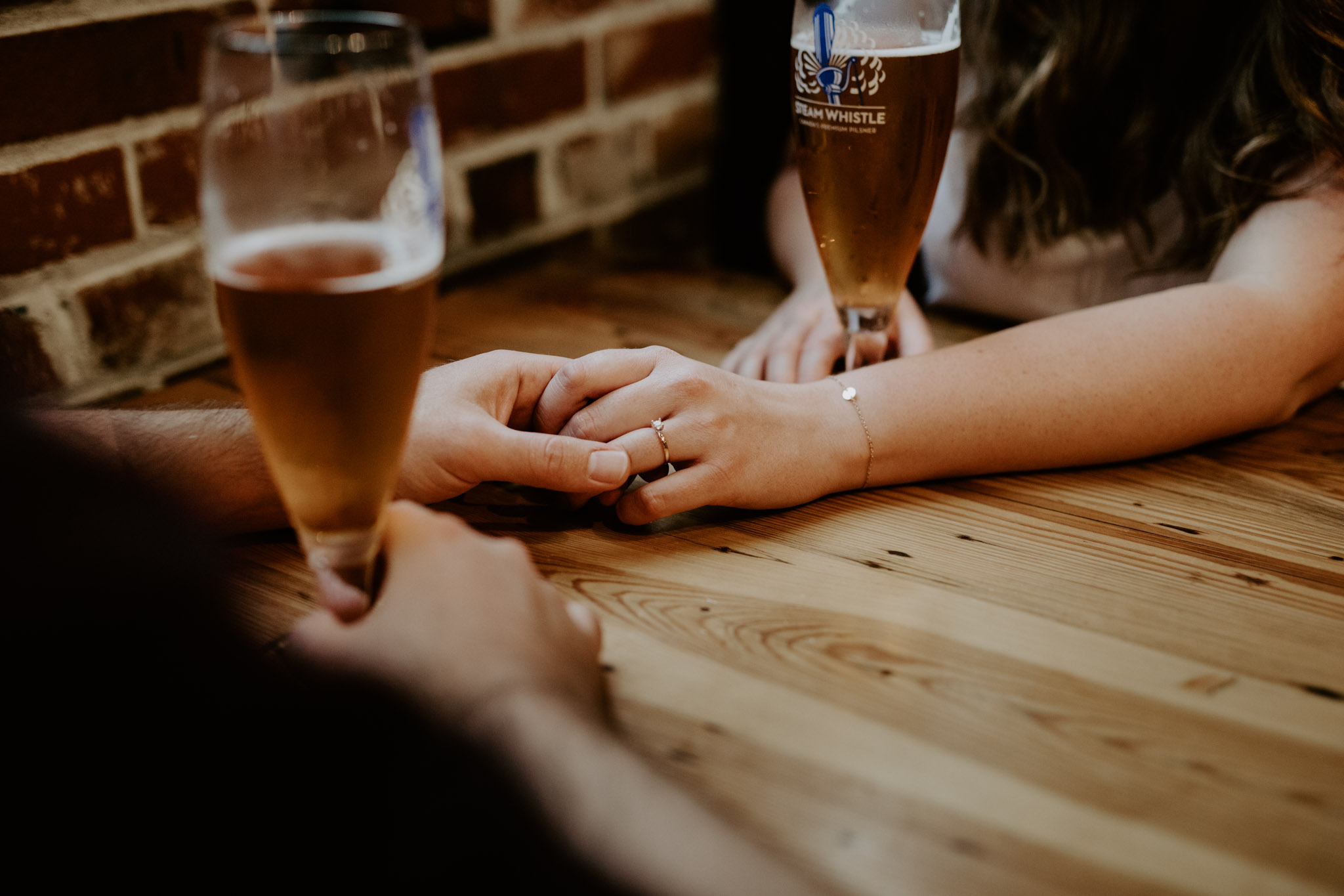 SteamWhistle Brewery Engagement - couple's hand touching while drinking beer