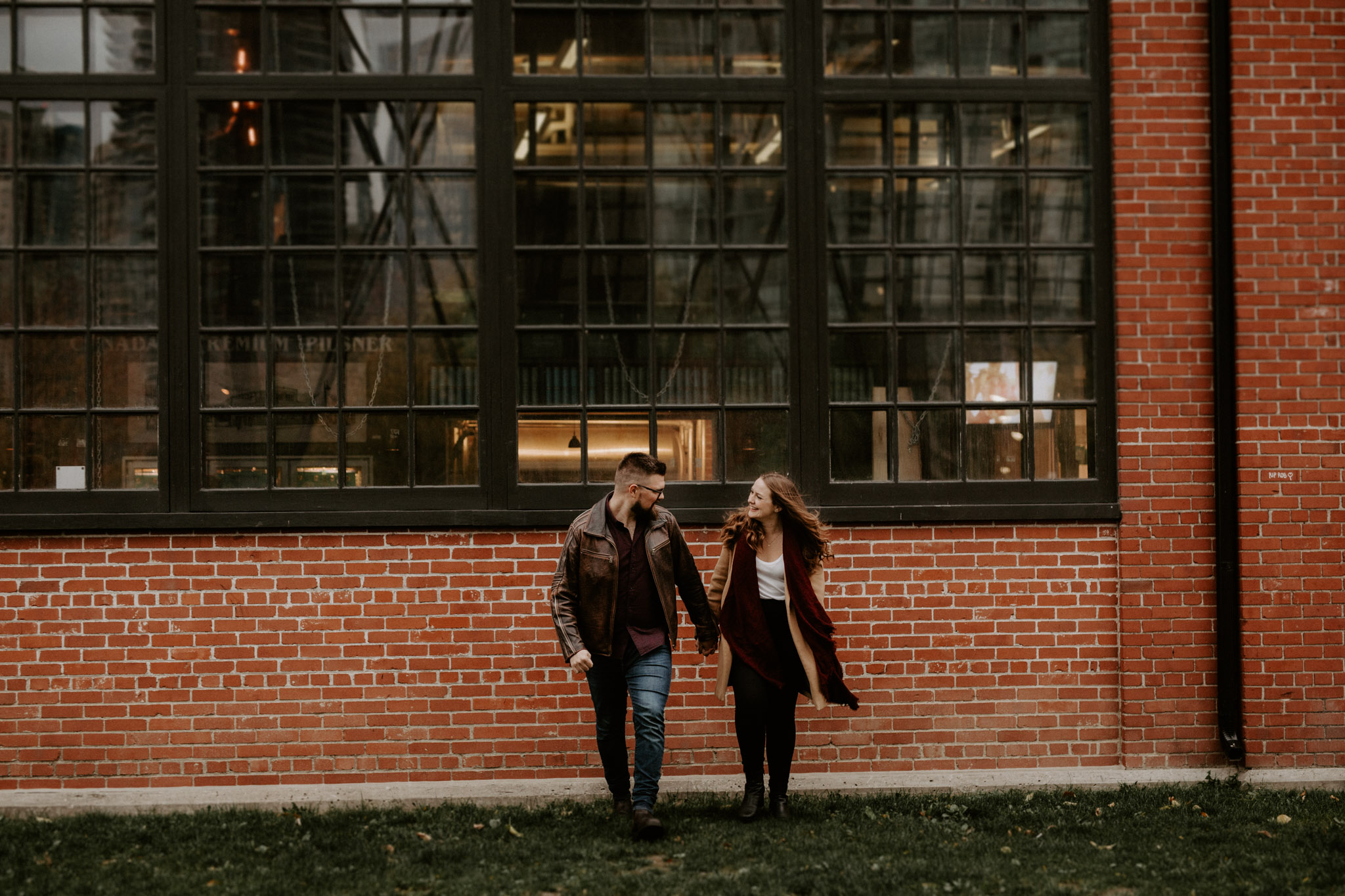 SteamWhistle Brewery Engagement - couple walking hand in hand near brewery