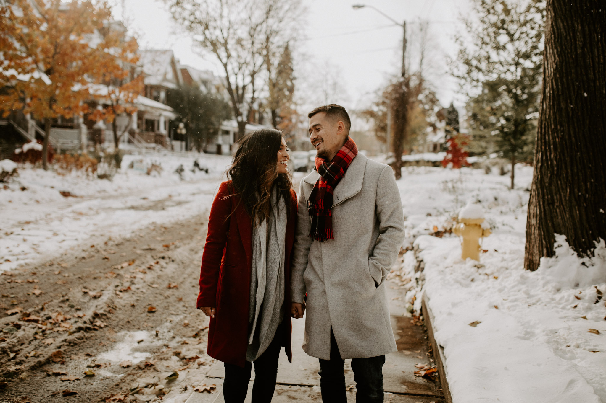 Winter Engagement in Toronto - woman in red coat and man in grey coat with red plaid scarf smile on snowy street