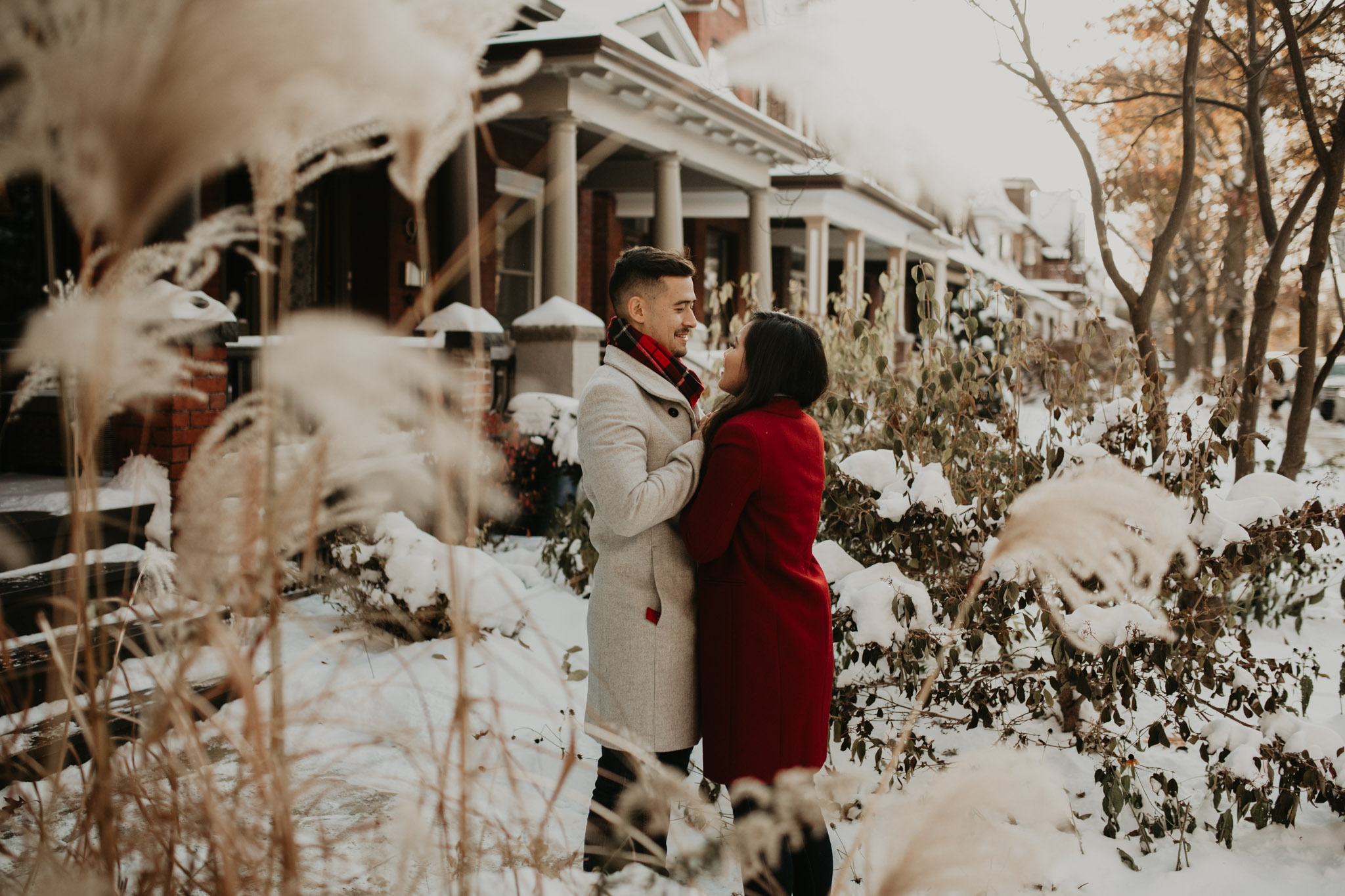Winter Engagement in Toronto - couple embrace in the snowy outside of house