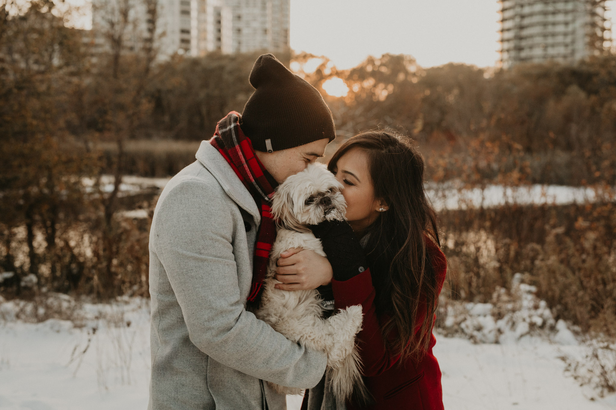 Winter Engagement in Toronto - couple kissing their dog in snowy park at sunset