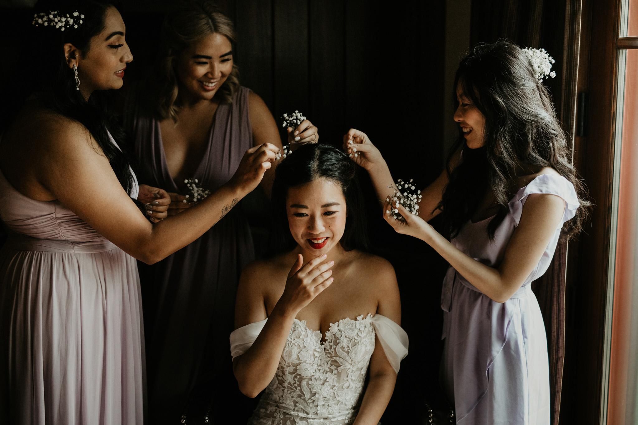 Serenity Cottage Wedding - bridesmaids putting flowers in brides hair