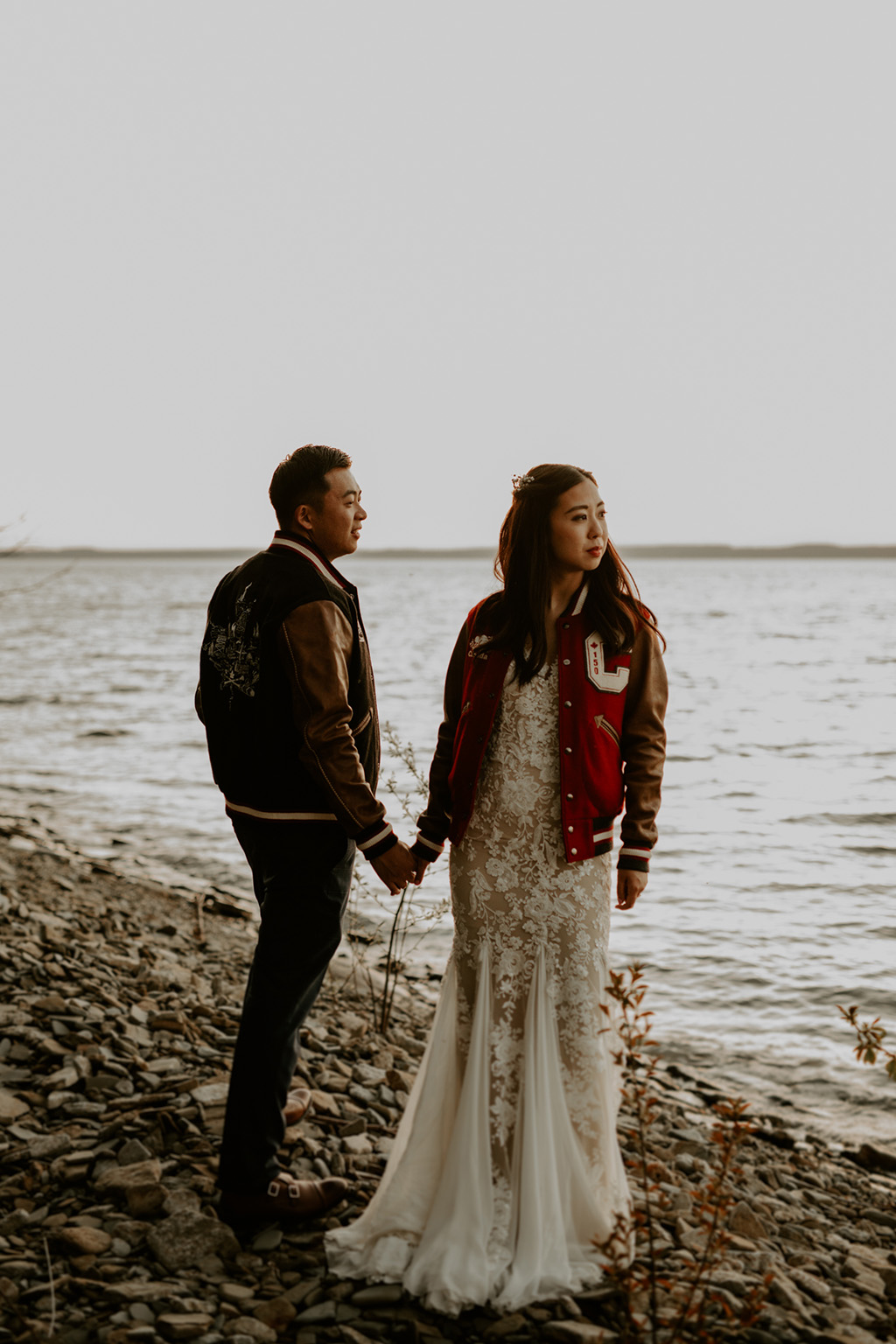Serenity Cottage Wedding - bride and groom in Letterman Jackets on the beach
