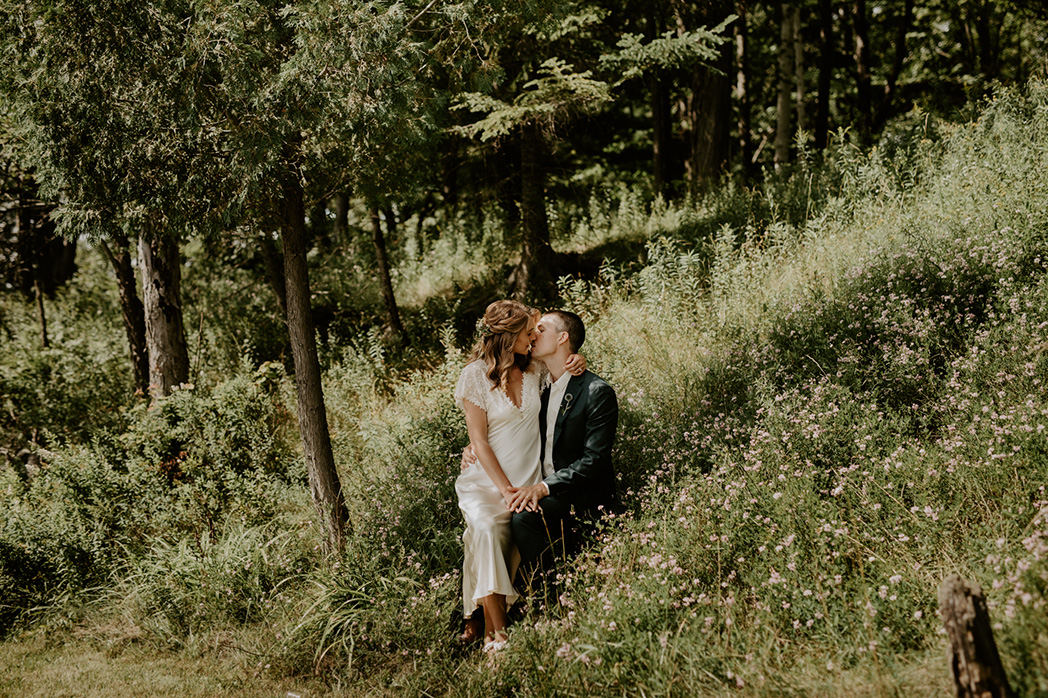 bride and groom sitting in grass at Lake of Bays wedding