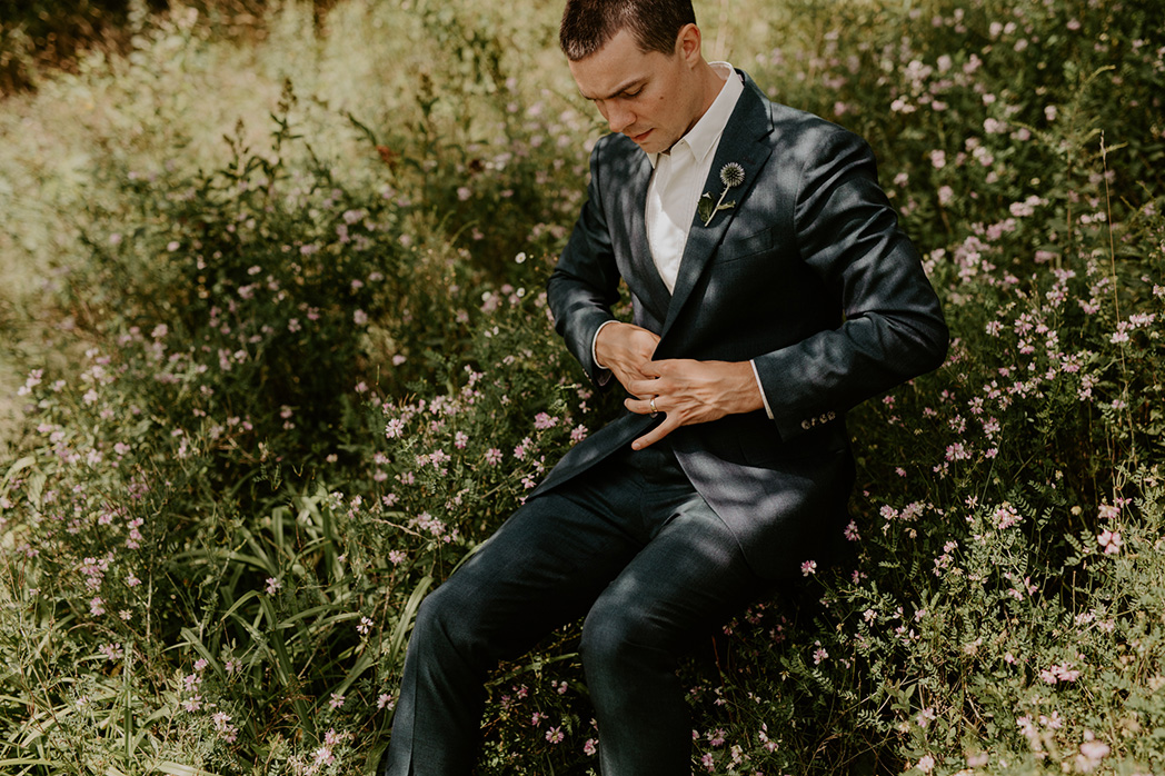 groom doing up jacket while sitting in grass