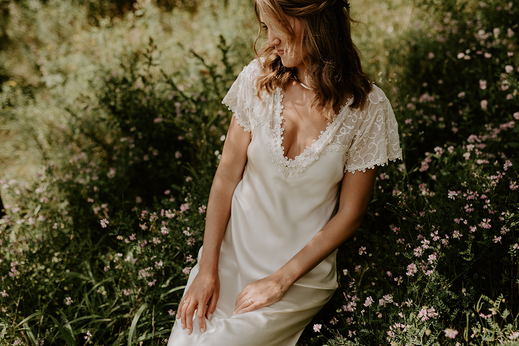 bride's dress while sitting in grass after wedding ceremony in Muskoka
