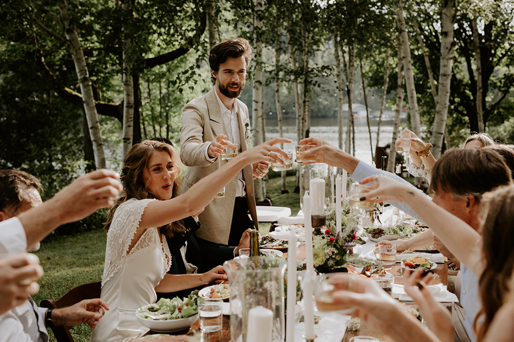 couple cheers at wedding reception in Lake of Bays